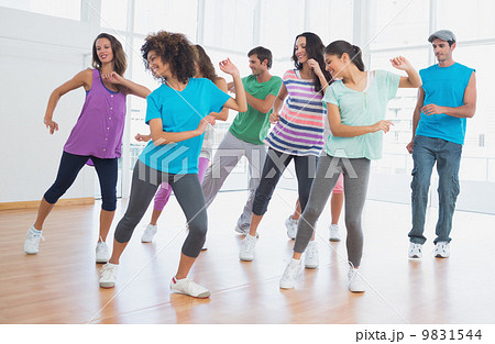 Fitness class and instructor doing pilates exercise