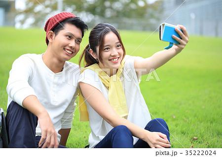 16c8368c57 大学生 キャンパスライフ カップル スマートフォンの写真素材 - PIXTA